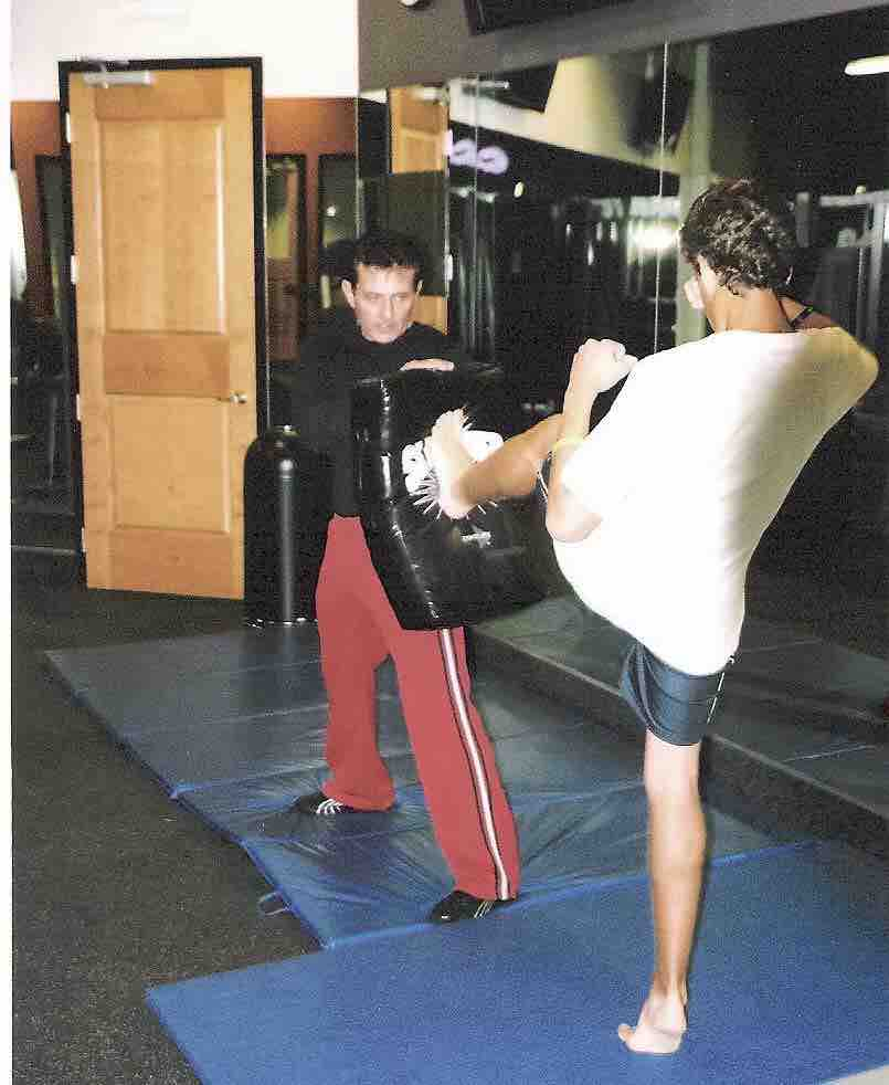 Image of a kickboxing trainer holding a kick sheild for a client performing a roundhouse kick