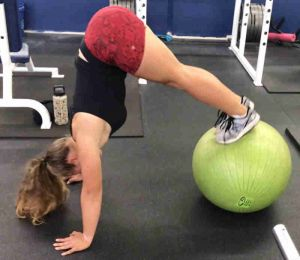 fitness female performing an advanced fit ball peak exercise