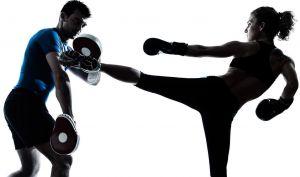 female kickboxer kicking a pad
