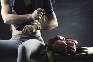 Female kickboxing client wrapping her hands while sitting on a bench
