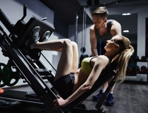 male personal trainer watching his female client use a leg press machine