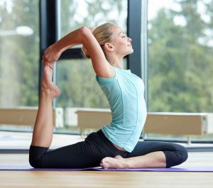 yoga instructor demonstrating a complex posture pulling her toes with leg back at 90 degree angle