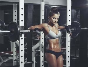 Fitness Model Resting Arms Over Barbell in Rack