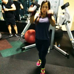Personal Trainer Client Starting Exercise Program using cable machine pulling both arms up to center of chest