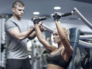 image of fitness client pressing weights above her head on a weight machine