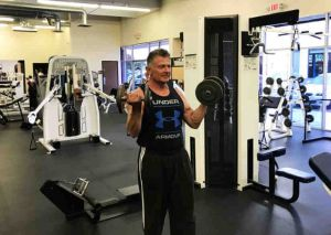personal trainer performing curls with dumbbells in a gym