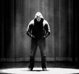 man standing on a stage with hands in his pocket wearing a hoodie