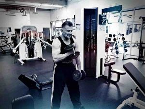 Personal Trainer Performing Dumbbells Curls in the Gym