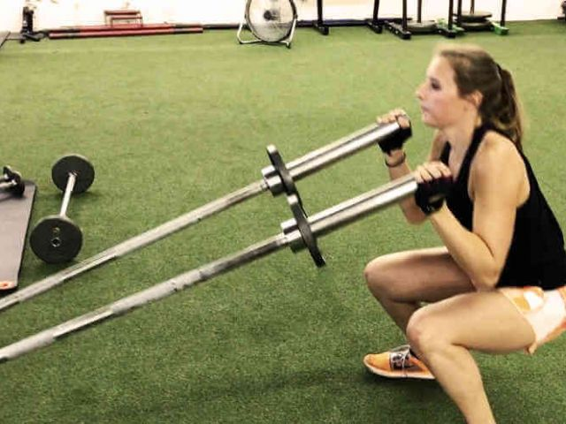 fitness client lifting two bars from a squat position