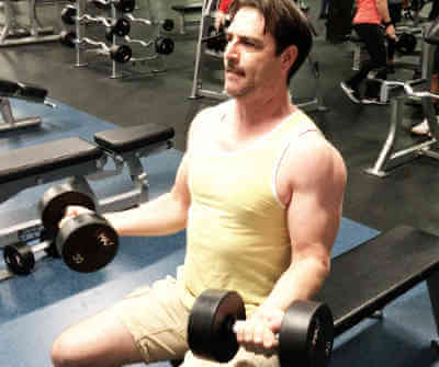 personal trainers client performing a bicep curl with dumbbells in seated position