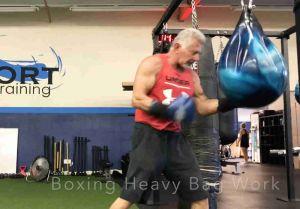 boxing trainer uppercutting a heavy bag