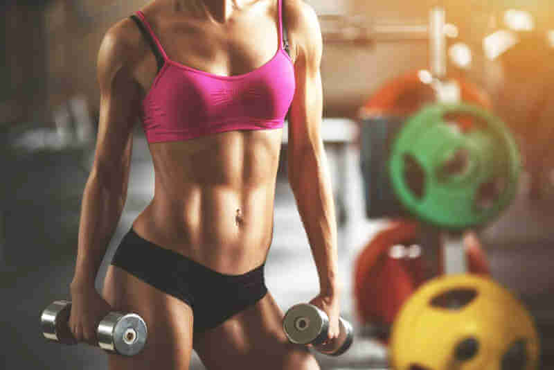 image of fitness girl holding a dumbbell in each hand down by her side