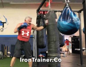 boxing trainer hook punching a heavy bag