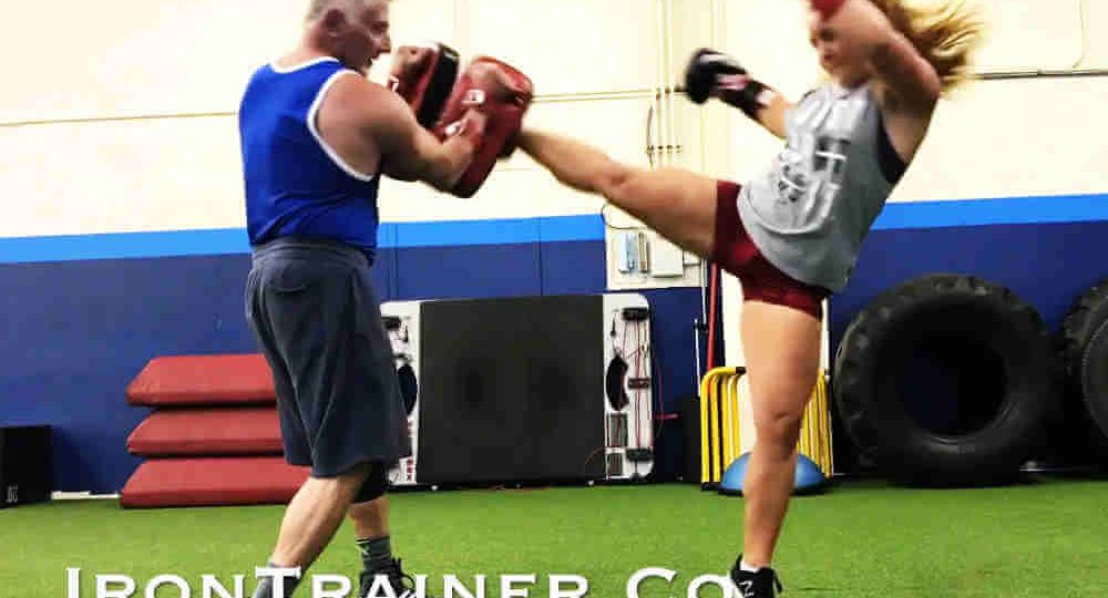instructor holding pads while client performs a roundhouse kick