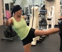 woman kicking a kickboxing pad during training