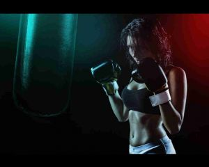 female with boxing gloves ready to hit a heavy bag