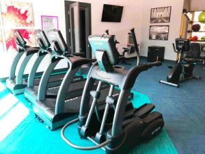treadmills and stationary bikes at apartment complex fitness room