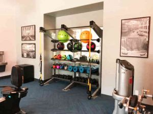 apartment gym with kettlebell rack and TRX Bands