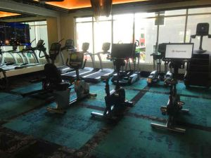 Cardio equipment room in apartment gym with windows overlooking the pool