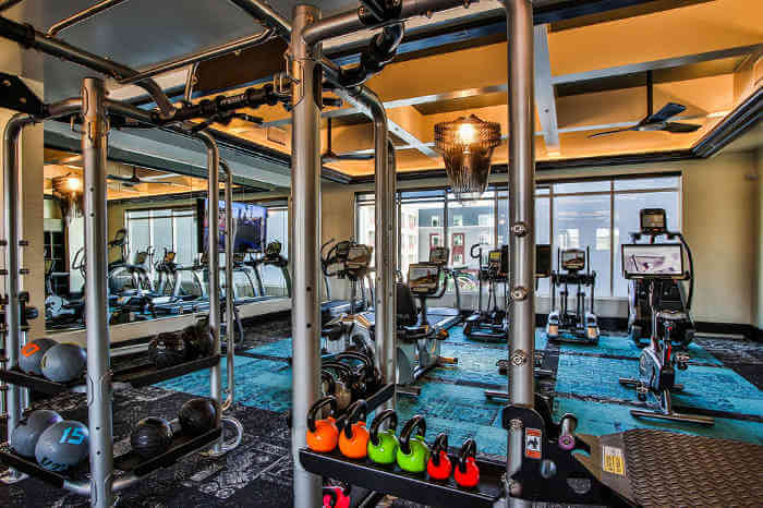 apartment gym with weight equipment and kettlebells