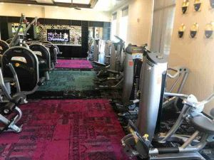 2 rows of weight machines image with television on wall
