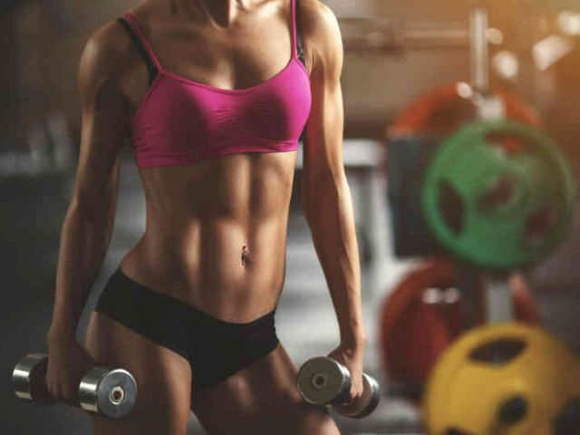 fitness girl holding two dumbbells wearing a fitness bra and small workout shorts
