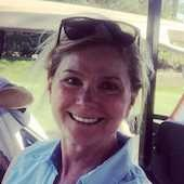 headshot of woman smiling sitting in a golf cart