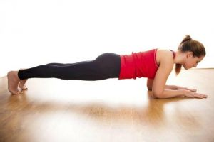 woman performing a plank exercise with back straight stabilizing body on forearms and ball of feet