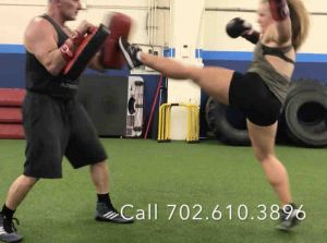 girl front kicking a thai pad while instructor holds the pads