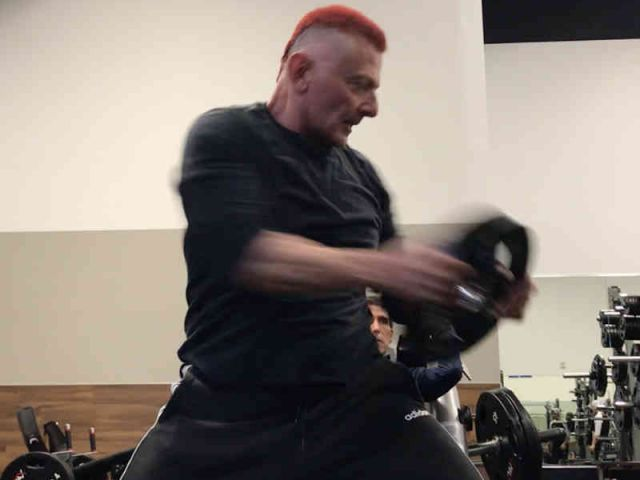 65 year old personal trainer swings a weight plate around his body and head
