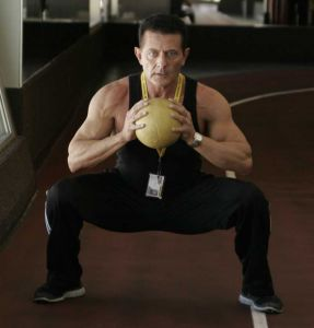 personal trainer in a low stance with feet wide holding a medicine ball in center of chest