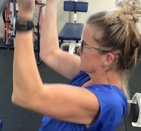 woman pulling a lat machine bar down while working out