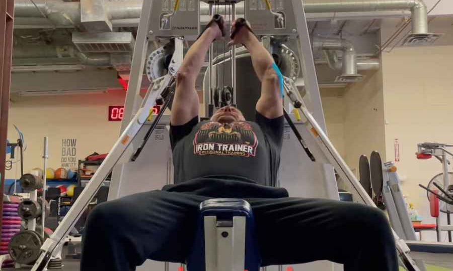 personal trainer on an incline bench performing a cable exercise for chest