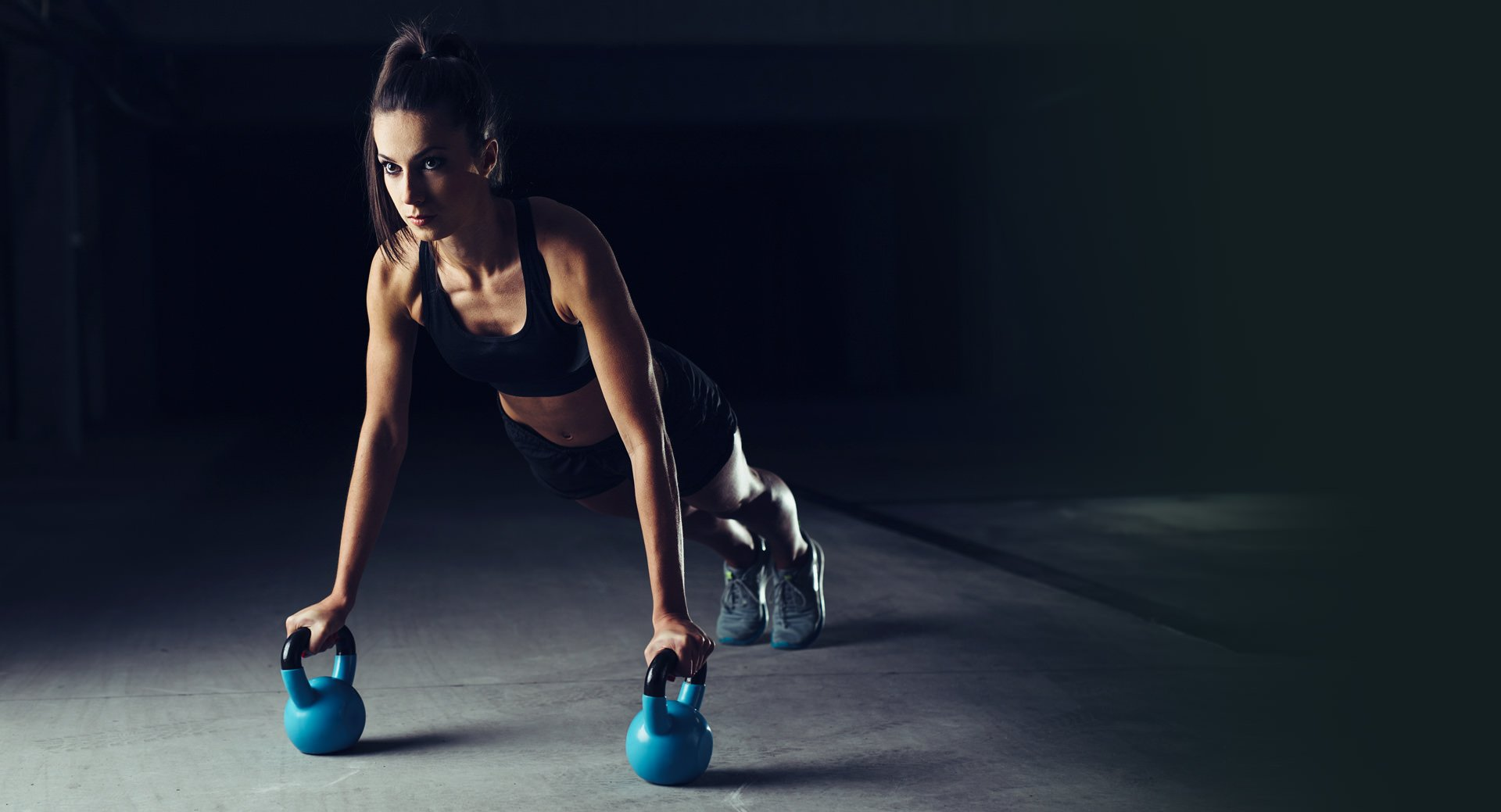woman performing push ups using kettlebells
